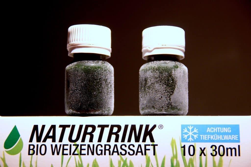 Naturtrink Weizengrassaft gefroren Fläschchen dunkler Hintergrund